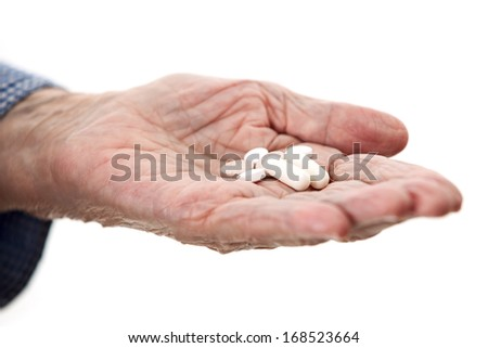 Closeup of senior hand holding medications over white - stock photo