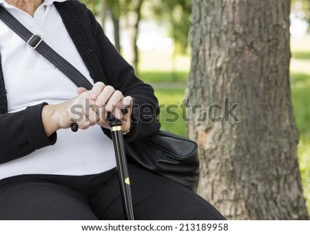 Closeup of senior hands holding cane. - stock photo