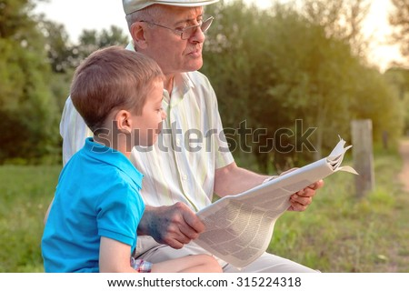 Closeup of senior man and cute child reading a newspaper sitting over a nature background. Two different generations concept. - stock photo