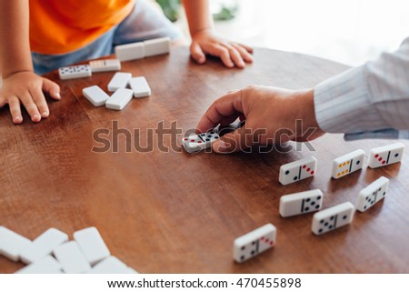 Closeup of senior man playing dominoes with little boy