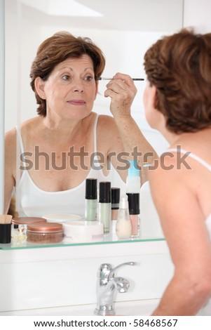 Closeup of senior woman putting makeup on - stock photo