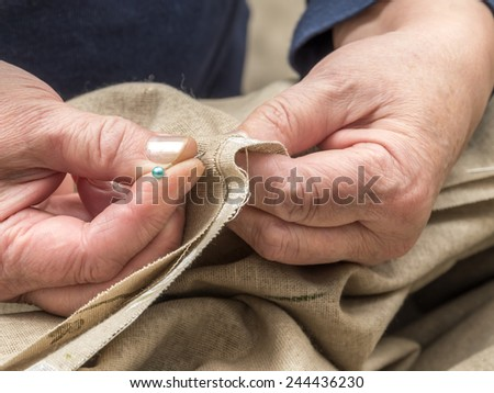 Closeup of senior woman's hands basting linen border using pins - stock photo
