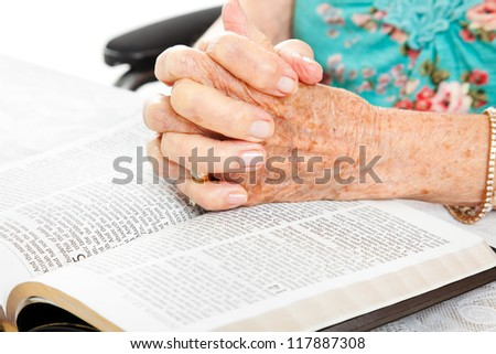 Closeup of senior woman's hands on bible, folded in prayer. - stock photo