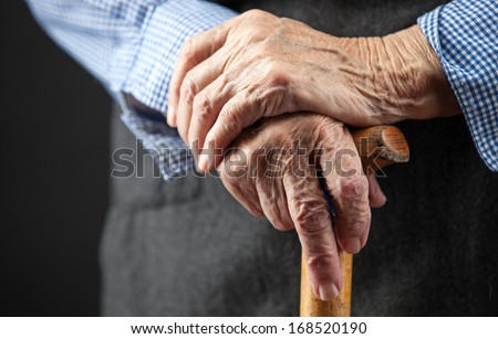 Closeup of senior woman's hands on wooden walking stick  - stock photo