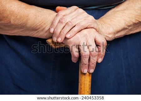 Closeup of senior woman's hands on wooden walking stick  - stock photo