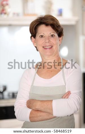 Closeup of senior woman standing in kitchen - stock photo
