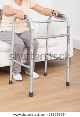 Closeup of senior woman using walking frame at nursing home - stock photo