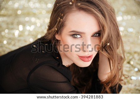 Closeup of sensual lovely young woman with long curly hair over glittering background
