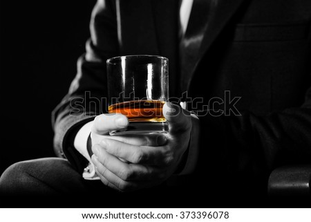 Closeup of serious businessman holding  whiskey illustrate executive privilege concept.  - stock photo