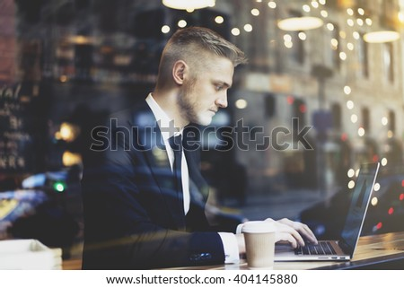 Closeup of serious businessman wearing black suit and using modern laptop in coffee shop, successful manager working in cafe and searching information in internet - stock photo