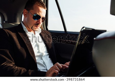Closeup of serious man working with laptop computer inside the car