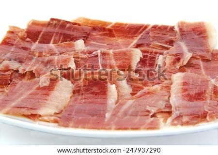 Closeup of serrano ham slices on a white dish. Jabugo. Spanish tapa - stock photo