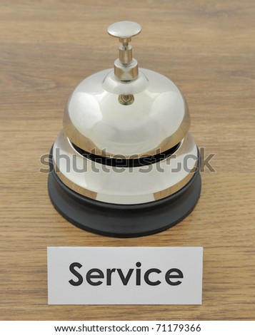 Closeup of service bell and sign on wooden oak desk