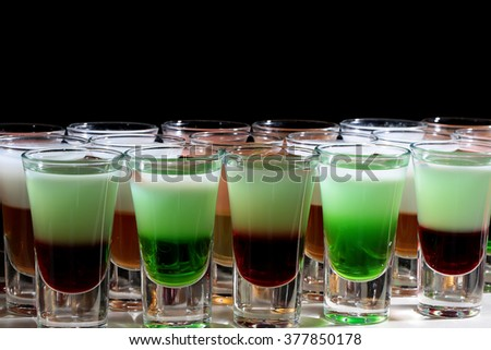 Closeup of set of many bright green red and white tasty strong alcohol shooters shots cocktail drinks in beautiful glasses menu for merry night party in club on black background, horizontal picture - stock photo