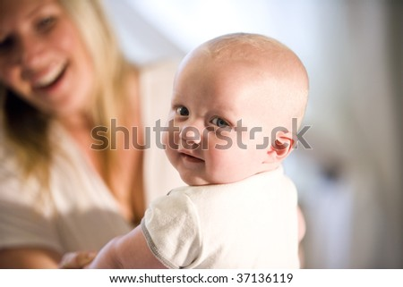 Closeup of seven month old baby looking over his shoulder, with mother in background - stock photo