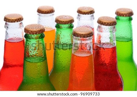 Closeup of several assorted flavors of soda pop. Orange, lemon lime, and strawberry soda bottles necks only over a white background. - stock photo