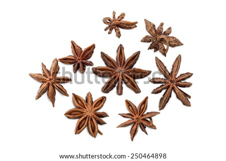 Closeup of several star anises (star aniseed or Chinese star anise) viewed from above, isolated on white background - stock photo