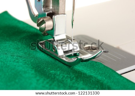 Closeup of sewing machine working part with  green cloth - stock photo