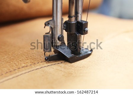 Closeup of sewing machine working part with leather