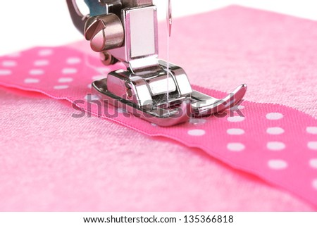 Closeup of sewing machine working part with  pink  cloth - stock photo