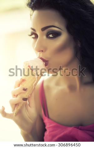 Closeup of sexual brunette attractive young lady with bright makeup eating cold dessert of red berry ice cream cone with mouth looking forward, vertical picture - stock photo