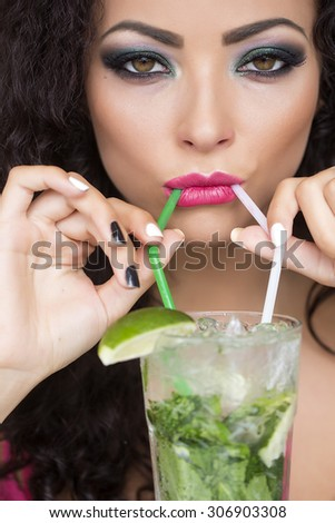 Closeup of sexual pretty brunette lady with curly hair and bright makeup drinking alcoholic mojito cocktail from mint soda light rum and lime with straw, vertical picture - stock photo