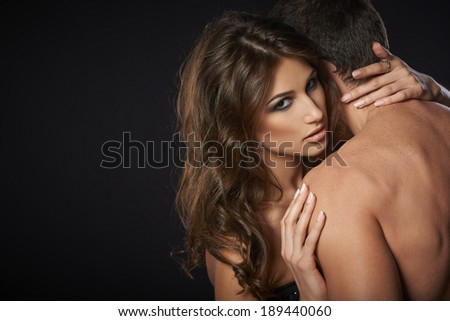 Closeup of sexy young couple embracing against black background