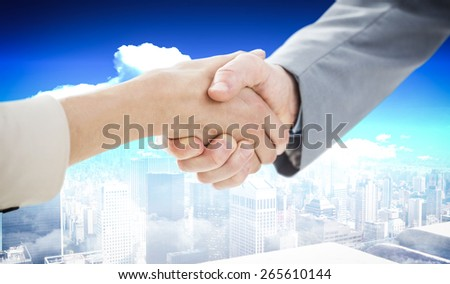 Closeup of shaking hands after business meeting against high angle view of city - stock photo