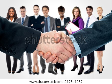 Closeup of shaking hands and business team in background