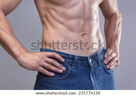 Closeup of shirtless Caucasian man wearing blue jeans with beautiful lean chiseled abdominal muscles on gray background - stock photo