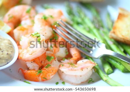 Closeup of shrimp dinner with asparagus, garlic bread and a grainy mustard and mayo sauce