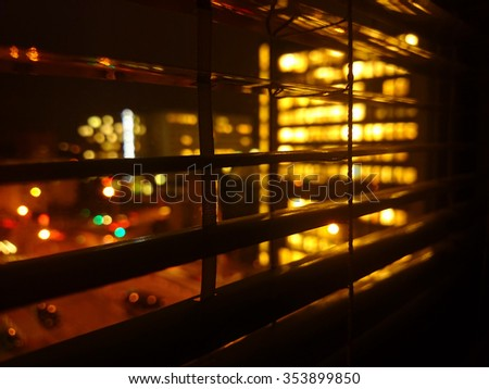 Closeup of shutter at night in office building  with view to lighten city - stock photo