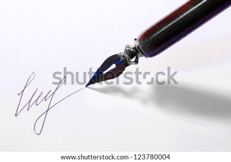 Closeup of signature (fake, not real) and ink pen, isolated on white