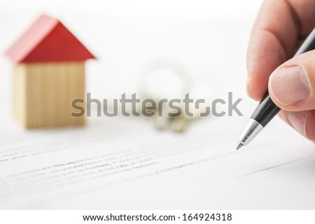 Closeup of signing contract of house sale. - stock photo