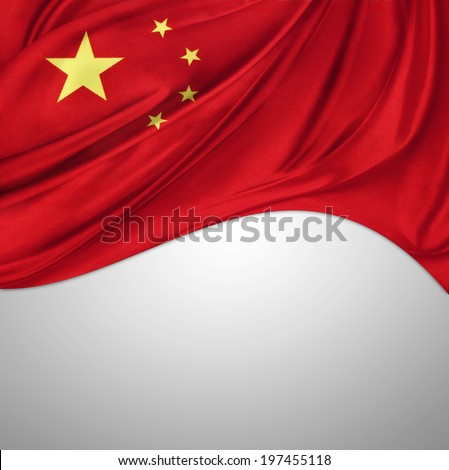 Closeup of silky Chinese flag on plain background - stock photo