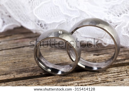 Closeup of silver wedding rings and lace on wooden table