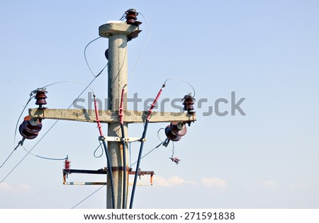 Closeup of simple three-phase electric pole with the sky in background - stock photo