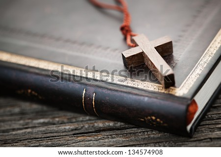 Closeup of simple wooden Christian cross necklace on holy Bible - stock photo