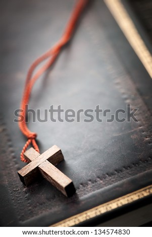 Closeup of simple wooden Christian cross necklace on holy Bible with copy space - stock photo
