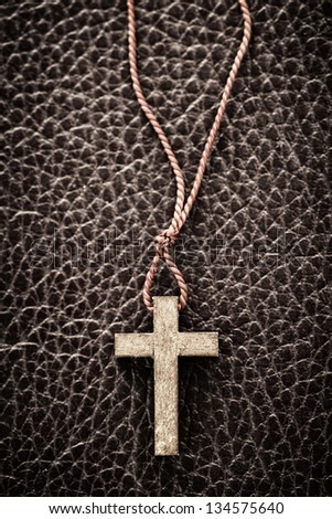 Closeup of simple wooden Christian cross necklace on leather bound holy Bible - stock photo