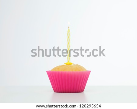 closeup of single cupcake, in pink silicone mould,with candle on top - stock photo