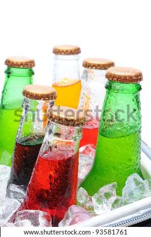 Closeup of six assorted soda bottles in an ice cooler with condensation. Vertical format over white with shallow depth of field.