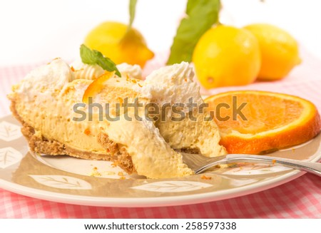 Closeup of slice of orange chiffon ice box pie with first bite on fork.  Garnished in orange zest and surrounded by citrus fruit. - stock photo
