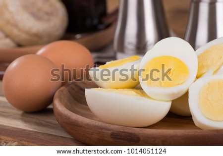 Closeup of sliced hard boiled eggs on a wooden plate