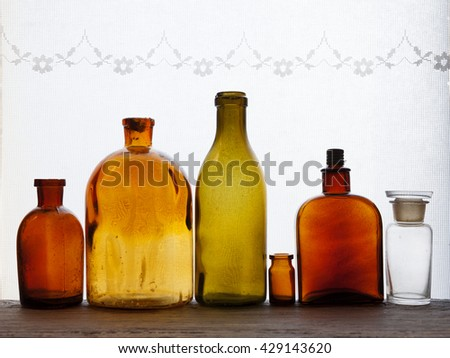 Closeup of small antique bottles at windowsill against daylight