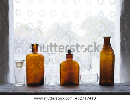 Closeup of small antique glass bottles at windowsill against daylight - stock photo