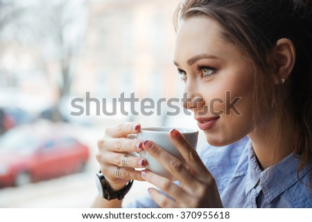 Closeup of smiling attractive young woman drinking coffee in front of the window - stock photo
