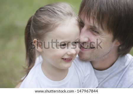 Closeup of smiling father cuddling daughter in park