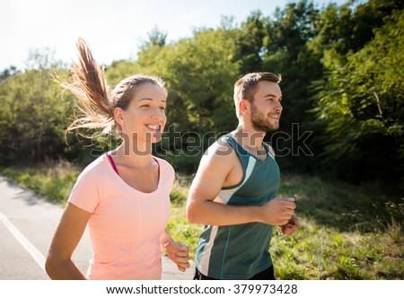 Closeup of smiling friends running together in summer sunny nature - stock photo