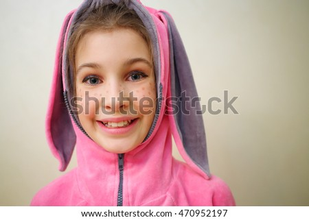 Closeup of smiling girl with flecks of sunlight in bunny suit indoor